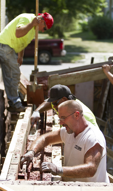 Workers pour concrete for the accesibility ramp on the Ingersoll House on Tuesday, July 17.