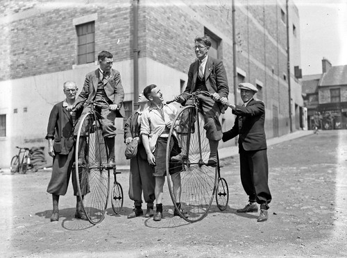 Group of men some wearing plus fours riding penny farthing bicycles