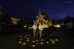 Women in traditional thai costume with candle at Ton Kwen Temple, Thailand.