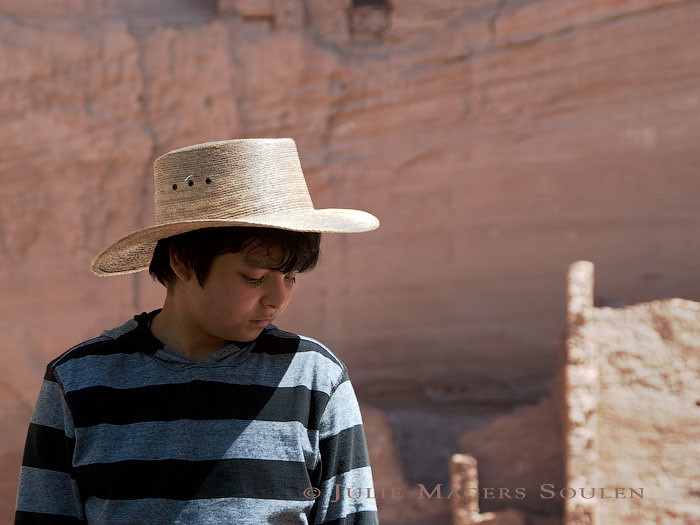 A native American boy gazes pensively at the ground
