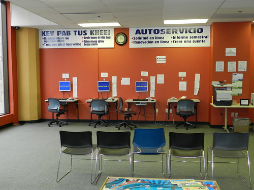 Robles computer wall with self-service signs in Spanish and Hmong. Established in the 1970's, the Robles Center located in Milwaukee Wisconsin, was the first social services office serving Milwaukee's predominantly Latino south side.