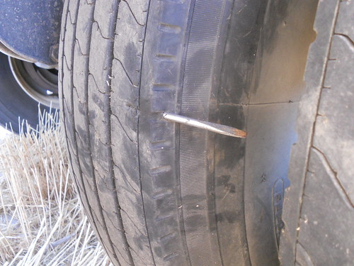 Part of a screw driver through the grain trailer tire