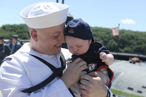 A Sailor  holds his three-month-old son for the first time moments after returning home from a six-month deployment.