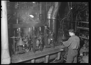 A worker taking a bottle off of an I. S. automatic blowing machine for testing, March 1937