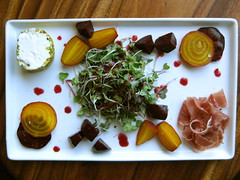 restaurant-style plating: roasted beet salad with blackberry-red wine vinaigrette, pistachio-crusted goat cheese, prosciutto and micro greens