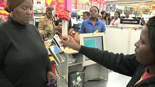 A SASSA grant recipient using her new SASSA Debit MasterCard card at point of sale to pay for her groceries