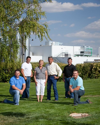 The McCarty family moved to the plains of western Kansas to allow their four sons to fulfill their dairy farming destiny. The first stage of a multi-year collaboration with The Dannon Company is in the background: a milk processing and condensing plant that helps to reduce the carbon footprint of the yogurt. Pictured left to right are Mike, Clay, Judy, Tom, David and Ken McCarty.  (Submitted photo.  Used with permission).