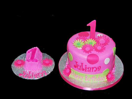 pink and green 1st birthday cake with daisies and polka dots