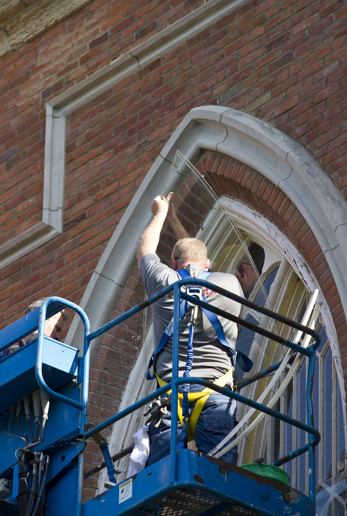 Workers from KnoxGlass remove glass on the third floor of Old Main so painting can be completed on the trim on Thursday, July 5.