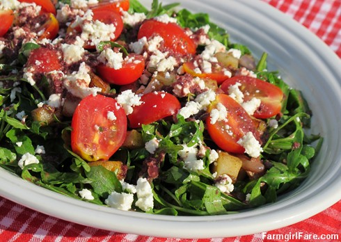 Arugula salad with pan-fried herbed potatoes, cherry tomatoes, feta cheese, and kalamata olive vinaigrette