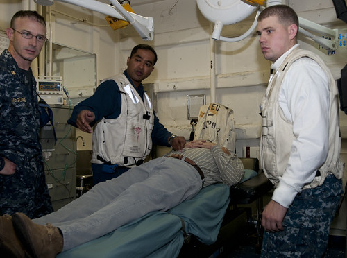 Lt. Cmdr. Ron McGuire (right) and Lt. Cmdr. Adnan Jaigirdar evaluate a 60-year-old patient
