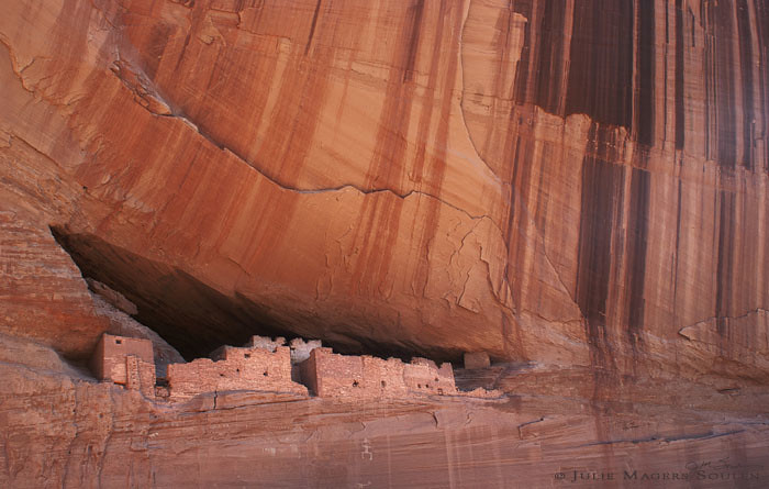Southwestern cliff dwelling, of an ancient prehistoric pueblo of the Anasazi in the American southwest nestled into a towering red rock cliff.