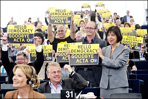 "MEPs from the Greens/EFA group hold up a sign saying ""Hello Democracy, Goodbye ACTA"""