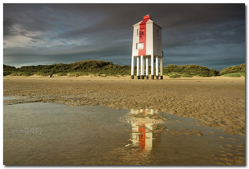 A reflection of a lighthouse in a puddle
