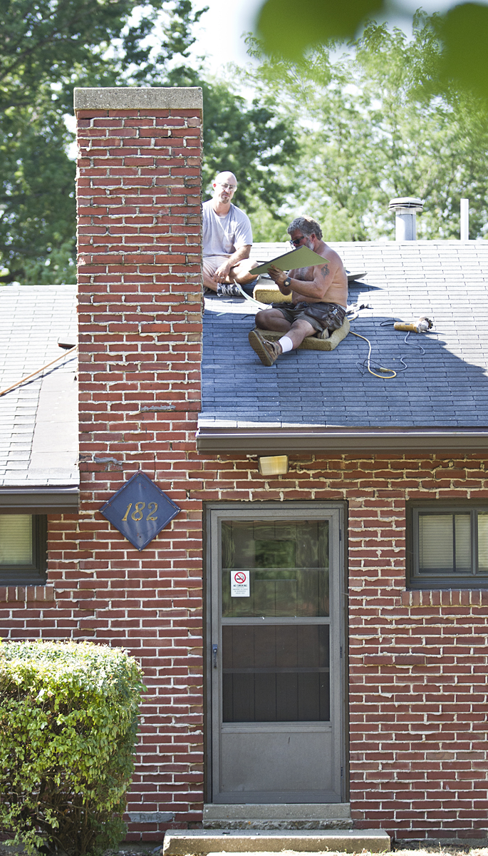 Despite temperatures reaching near 100 degrees and a heat index well over 100, two workers continue their work on the roof of Wilson House on Tuesday, July 17. Photo by John Williams