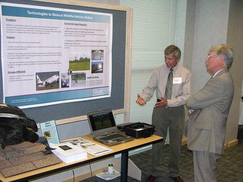 A researcher from USDA-APHIS' National Wildlife Researcher Center discusses new technologies for reducing bird-aircraft collisions with a stakeholder at an event in 2010.
