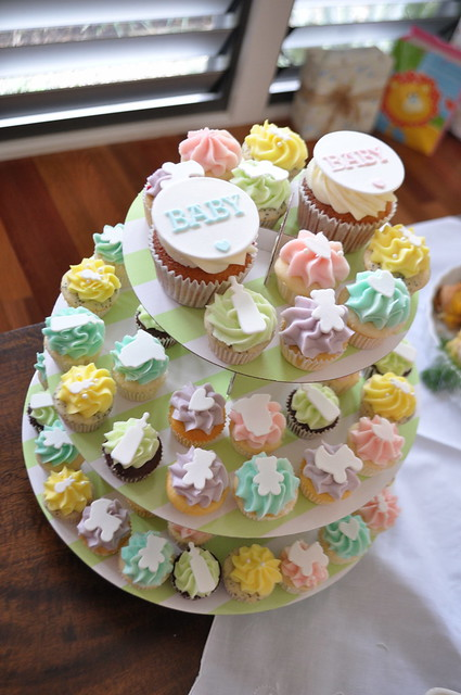 Pastel baby shower cupcakes. A mix of mini cupcakes and two regular cupcakes ...