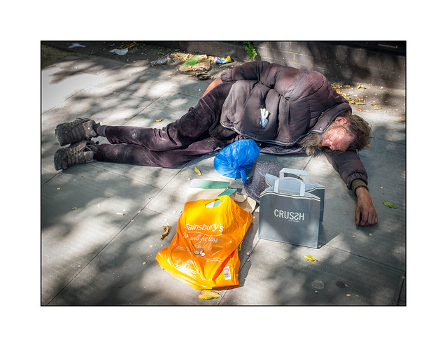 Homeless man, resting in the heat of the day, North London, England.