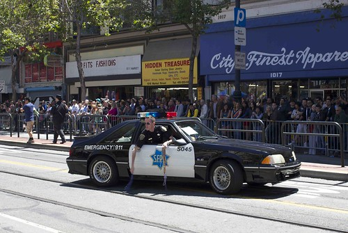 SFPD patrol car, with officer leaning out window, with handfuls of colorful beaded necklaces