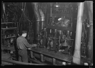 Second shot of a worker taking a bottle of of an I. S. automatic blowing machine for testing, March 1937