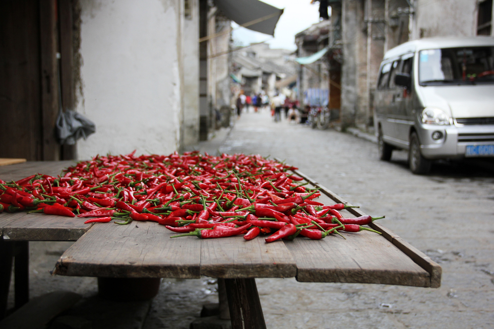 Vibrantly red chillies drying on the ancient streets of Xingping, China
