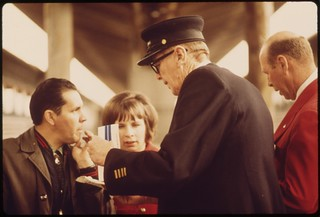 Conductor and Amtrak employee (in red blazer at right) answer questions by passengers concerning schedules, May 1974