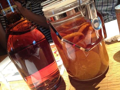 テーブルの上にはブランディーとオレンジがつけてある瓶が。@新 つくって楽しい!ブランデースプリッツァー講座
