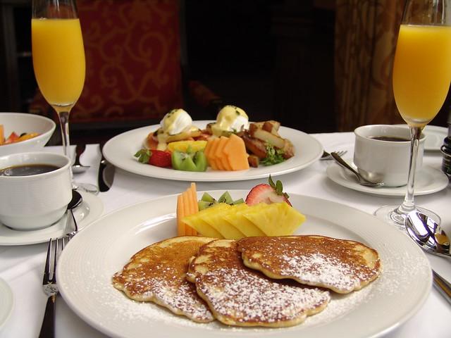 colazione servita sul tavolo con frutta, pancakes e posate