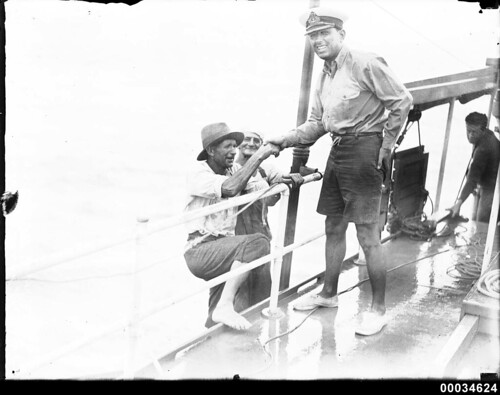 Civilians climbing aboard a vessel with an officer lending a hand, 1890-1953