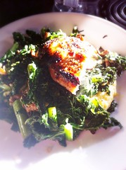 half a pan fried chicken breast over sautéed kale…
