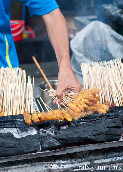 satay chicken skewers on charcoal bbq at lau pa sat festival market hawker market singapore