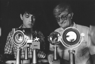 Physics Professor Walter Ogier working with a student on an apparatus designed to create holograms in 1983