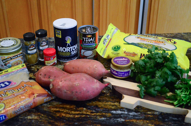 All the ingredients required to make Sweet Potato Coconut Curry Soup, arranged on a counter top.