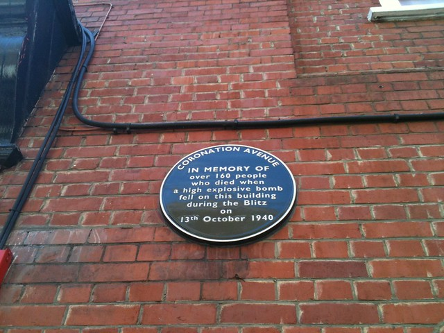 Black plaque № 11634 - Coronation Avenue  In memory of over 160 people who died when a high explosive bomb fell on this building during the blitz on 13th October 1940.