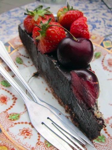 Close-up of a fudgy chocolate tart on a plate. It's covered with strawberries and cherries.