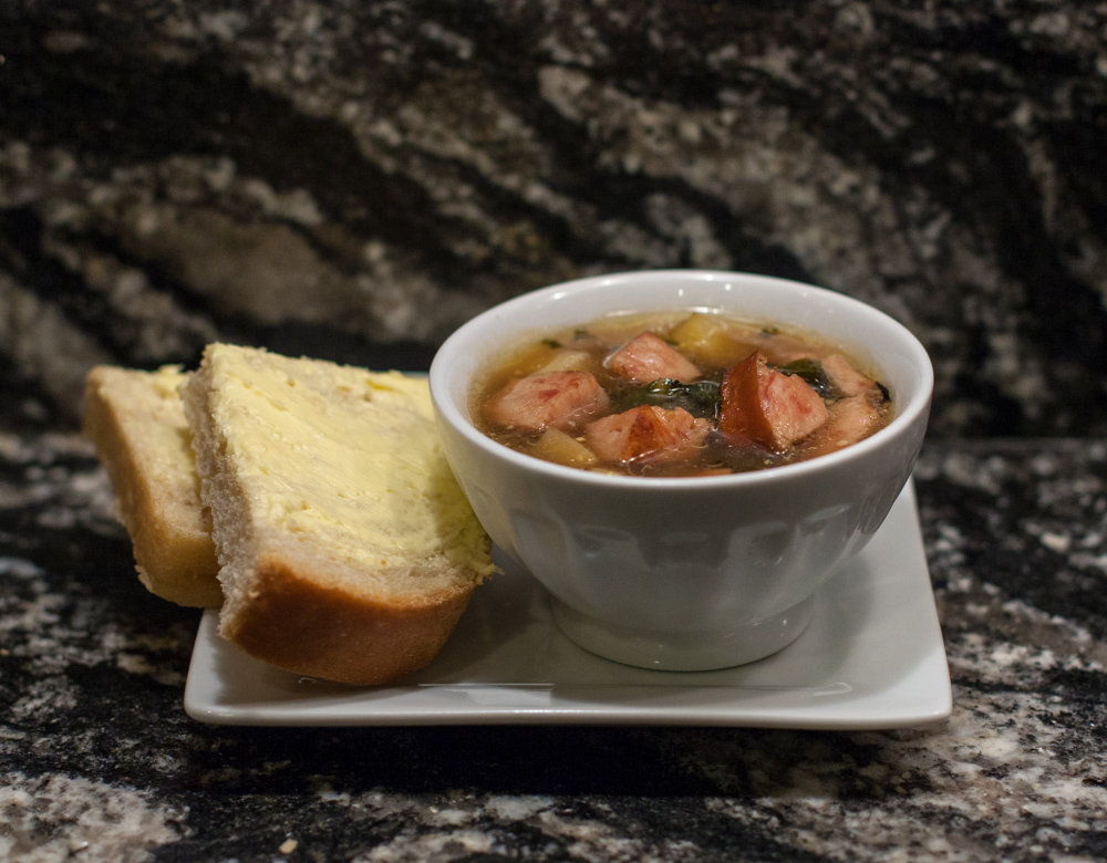 Kielbasa and greens soup with a slice of homemade bread