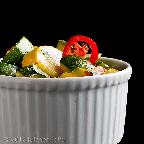 Summer Squash in Tomato Curry Sauce in White Ramekin, Black Background