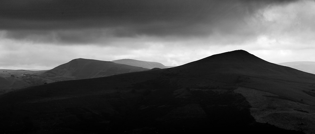 A black and white photo of mam tor in the peak district national park, showing the mountain silhouette