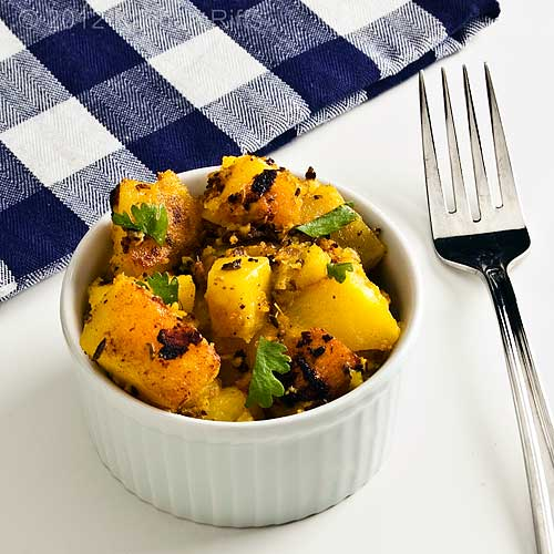 Spicy Potatoes with Ginger and Garlic in White Ramekin, with Napkin and Fork