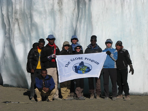 Taking a picture at the summit with one of Kili's glaciers