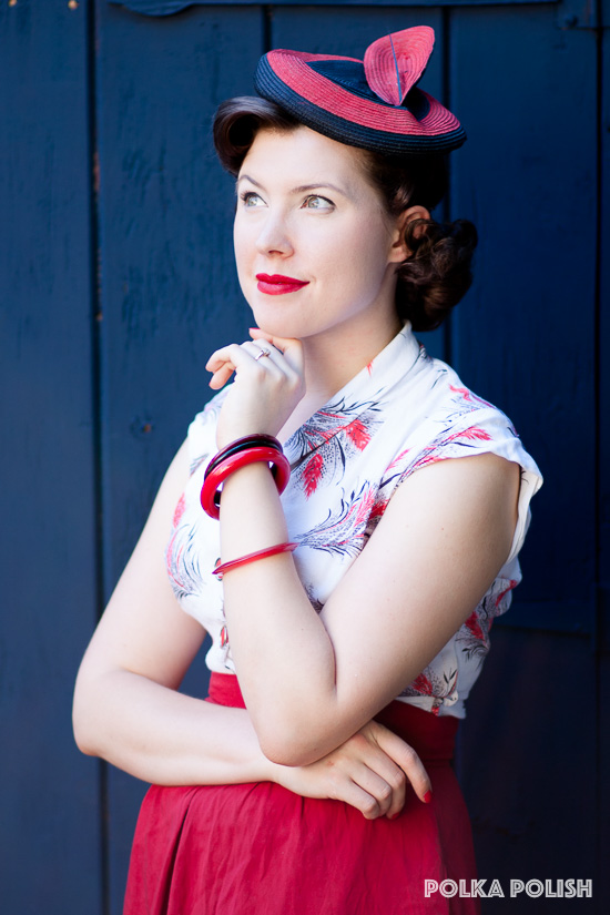 1940s wheat-print dress paired with a red skirt, bakelite, and bulls-eye vintage hat