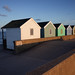 Back of huts at sunset by Laurence Cartwright