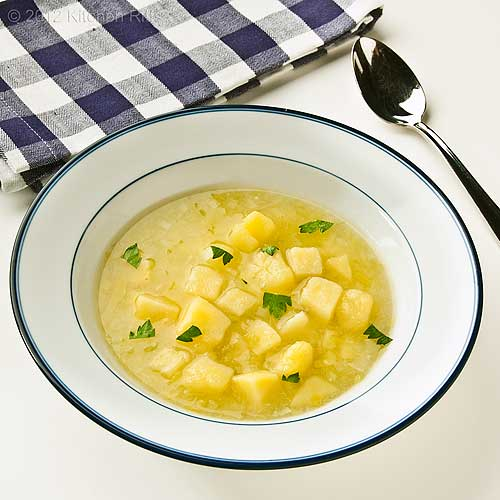 Leek and Potato Soup in Bowl with Napkin and Spoon, White Background