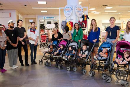 designers and moms with strollers standing in a Babies R Us