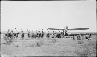 Aborigines and stockmen on horseback in front of de Havilland DH61 Giant Moth biplane airliner G-AUHW 'Canberra' wave goodbye to Les Holden and crew, Flora Valley, Western Australia, 23 April 1929.