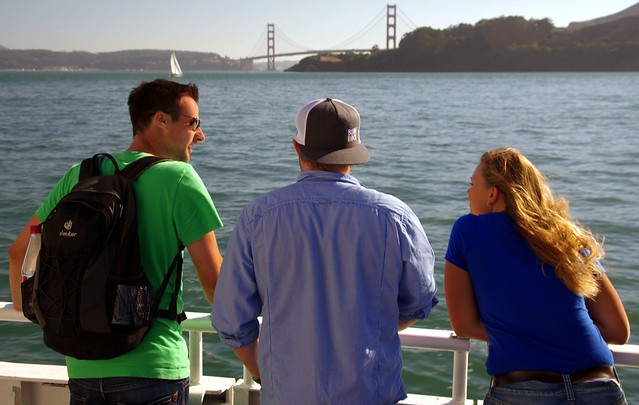 Tourists enjoying Sausalito to San Francisco ferry ride, Golden Gate Bridge in background