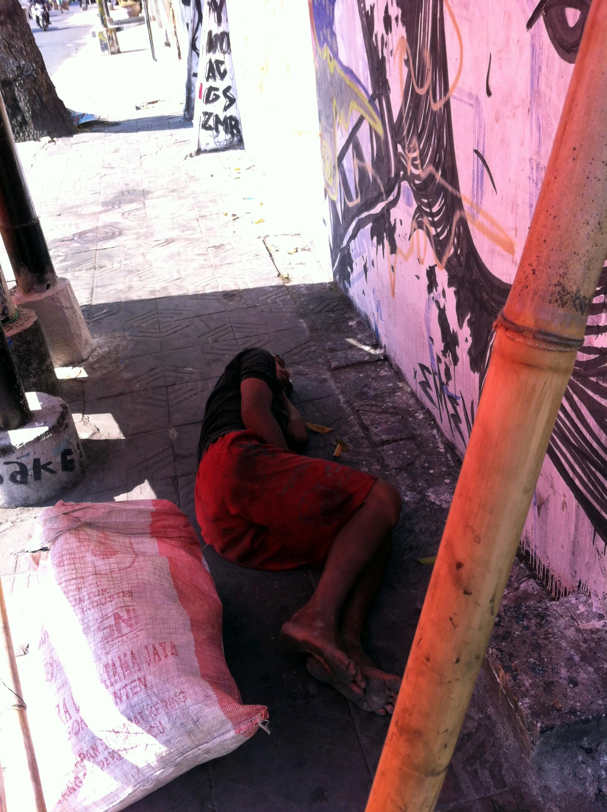 A plastic bottles collector sleeping on the sidewalk