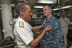 Adm. Cecil Haney pins USS Mustin's Sonar Technician (Surface) 1st Class Blair Ransom with the enlisted surface warfare device on the ship's mess decks following an all hands call with the crew in Malaysia, Sept. 27.  (U.S. Navy photo by Mass Communication Specialist 2nd Class Devon Dow/Released)