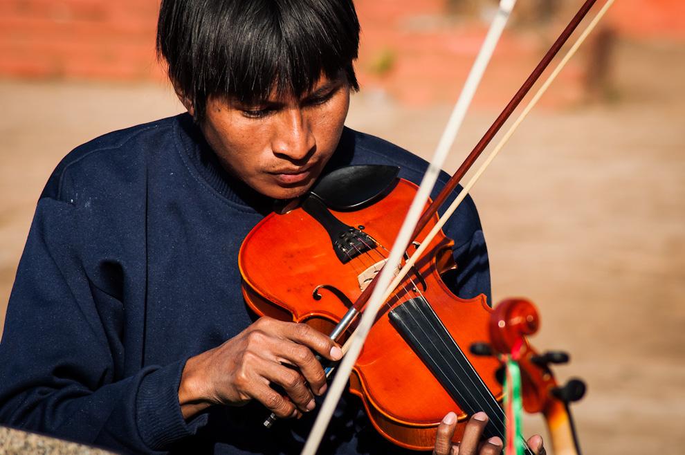 """Un joven indígena practica con su violín en el Colegio J. F. Kennedy junto a sus compañeros en la mañana del 21 de Julio durante la preparación del megaconcierto que se llevaría a cabo esa noche en la ciudad de Caacupé. El proyecto """"Sonidos de la Tierra"""", gracias a las ayudas que recibe, hoy en día puede alcanzar a cualquier persona que ame la música sin importar su origen ni condición. (Elton Núñez)"""
