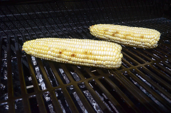 Two cobs of corn sitting on a grill.